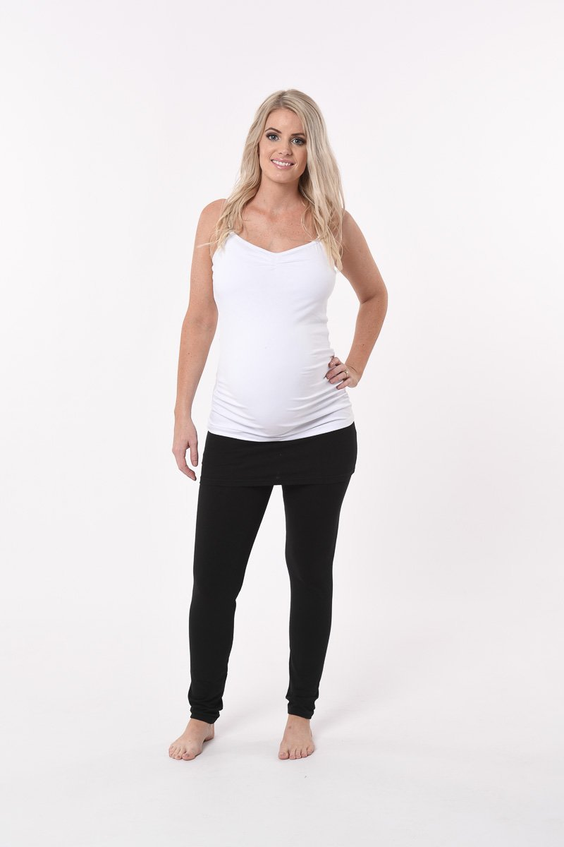Pregnant woman with black maternity pants and white maternity top